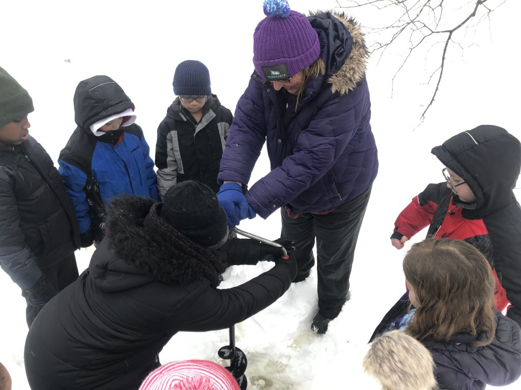 Dodge Nature Center Volunteer Leslie Krona helps elementary students drill a hole in the Farm Pond ice.