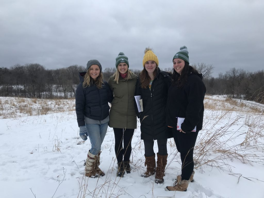 Dodge Nature Center's 2019-2020 class of Naturalist Fellows in the prairie on the Main Property in West St. Paul.