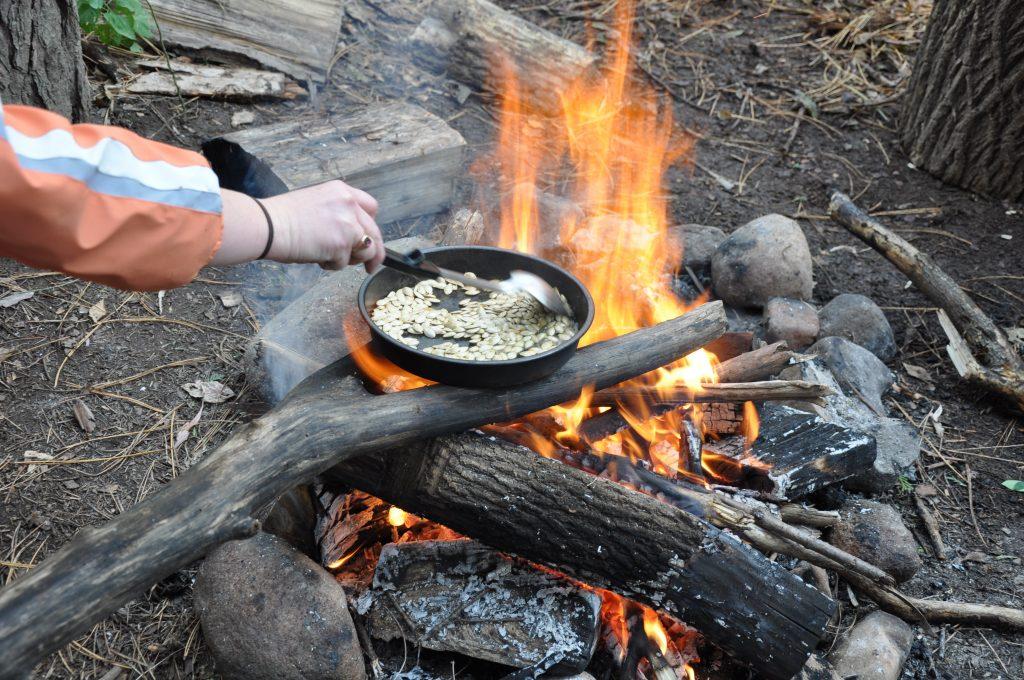 A roaring fire heats a cast iron of roasting pumpkin seeds.