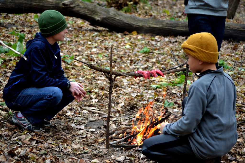 Two Dodge Nature Center campers roast strips of meat over a campfire in the woods.