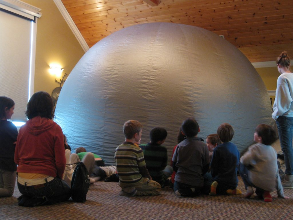 Students sit and wait patiently to enter the inflated Star Lab.